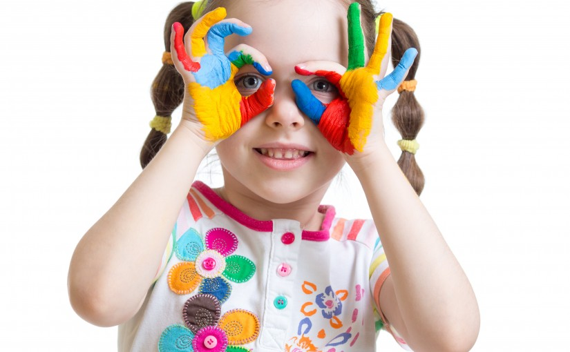 Four year old child girl with hands painted in color paints isolated